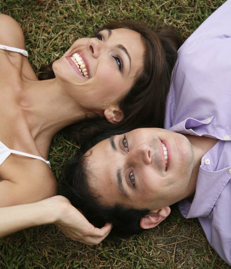 Smiling couple laying on grass