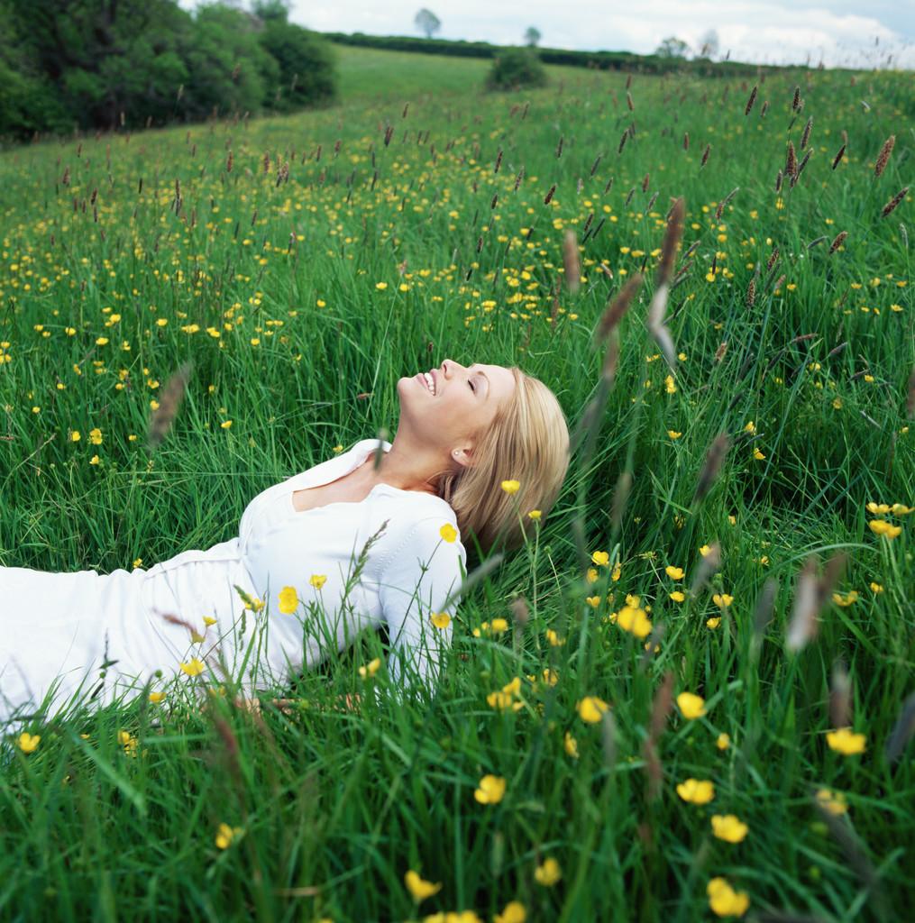 Blond woman lying in field